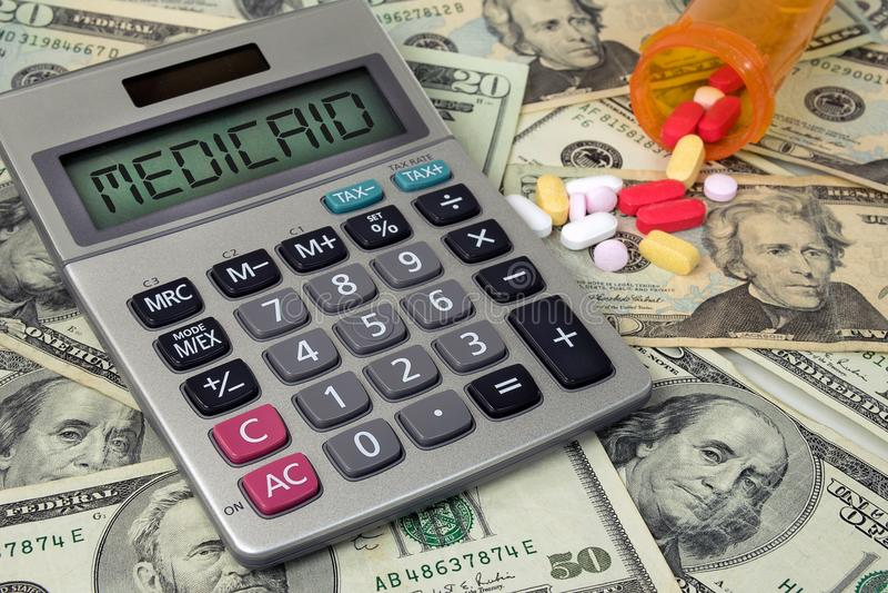 医疗补助在计算器的文本标志有药片和金钱的 免版税库存图片