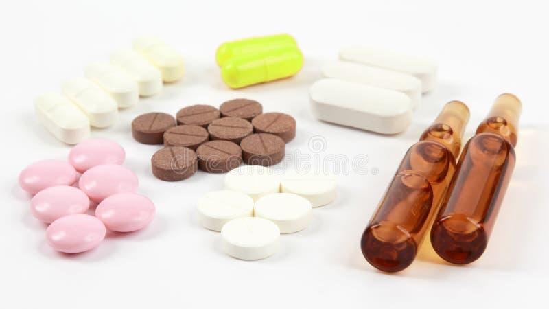 医药片剂,射入的一次用量的针剂在白色背景 免版税库存照片