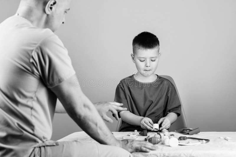 医院工作者 ?? 孩子小医生坐桌医疗工具 E 儿科医生概念 r 免版税库存照片