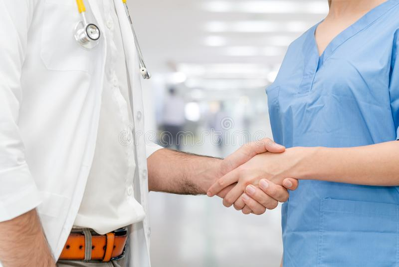 医院握手的医生与另一位医生 免版税库存照片