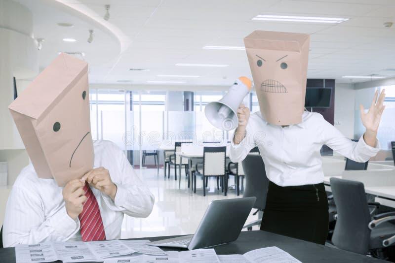 匿名女商人尖叫对使用扩音机的雇员在办公室 库存照片