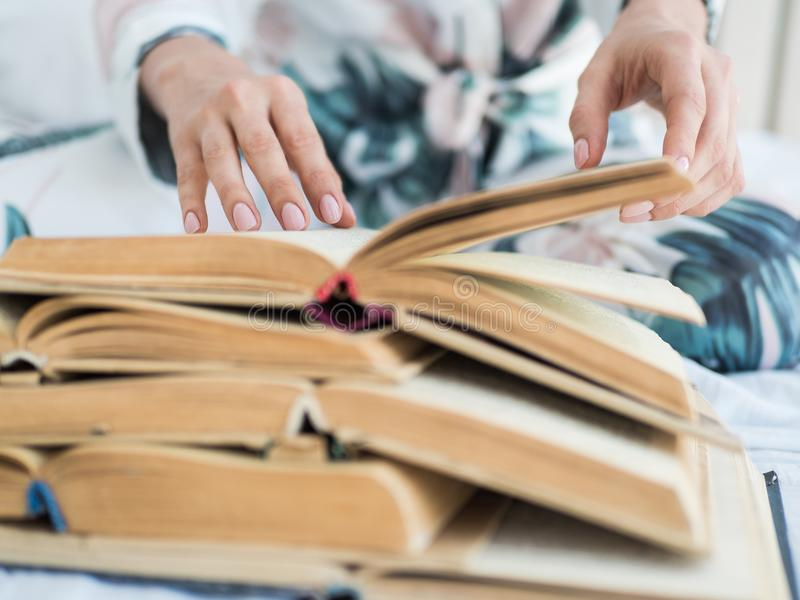 匿名妇女在绿色偶然羊毛毛线衣藏品开放蓝皮书在手上穿戴了充满爱对读 关闭 免版税图库摄影