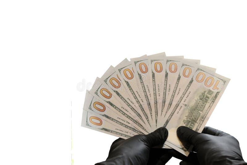 十一百元钞票和黑橡胶手套 一千美元作为一个爱好者在男性手上 背景查出的白色 复制 库存图片