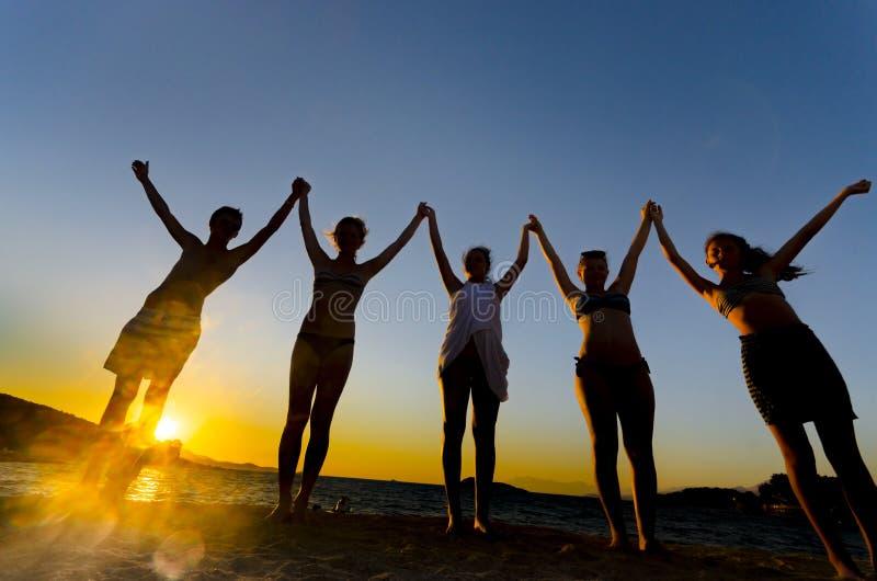 十几岁剪影在日落在海滩,幸福概念的 免版税库存照片