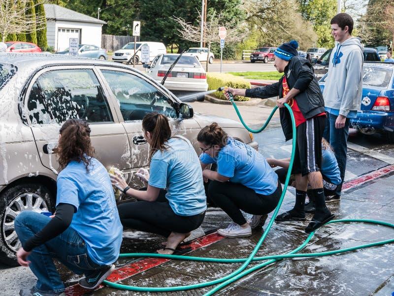 十几岁慈善募捐人的洗涤汽车 库存照片