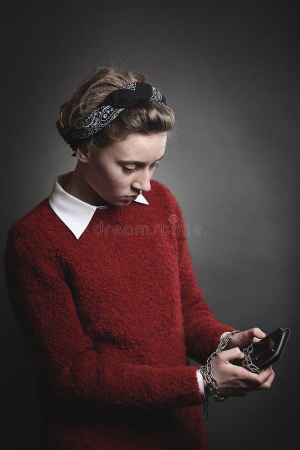 十几岁的女孩使上瘾对智能手机 免版税库存图片