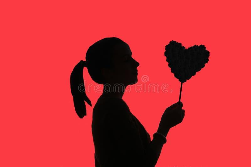 十几岁的女孩剪影有马尾辫的,拿着花心脏我 库存图片