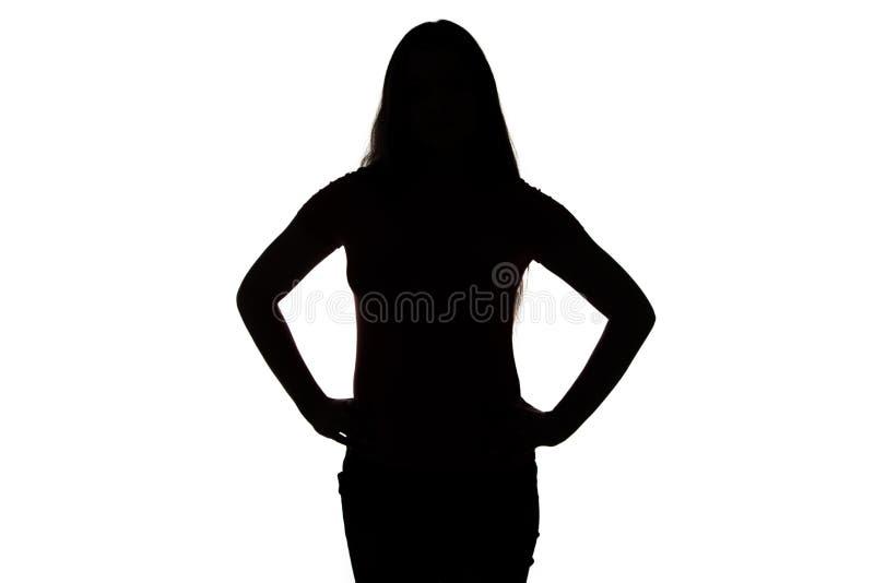 十几岁的女孩剪影用在臀部的手 免版税图库摄影