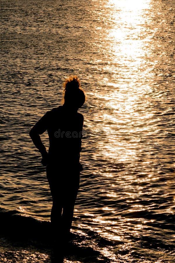 十几岁的女孩剪影美丽的海滩的在日落期间 库存照片