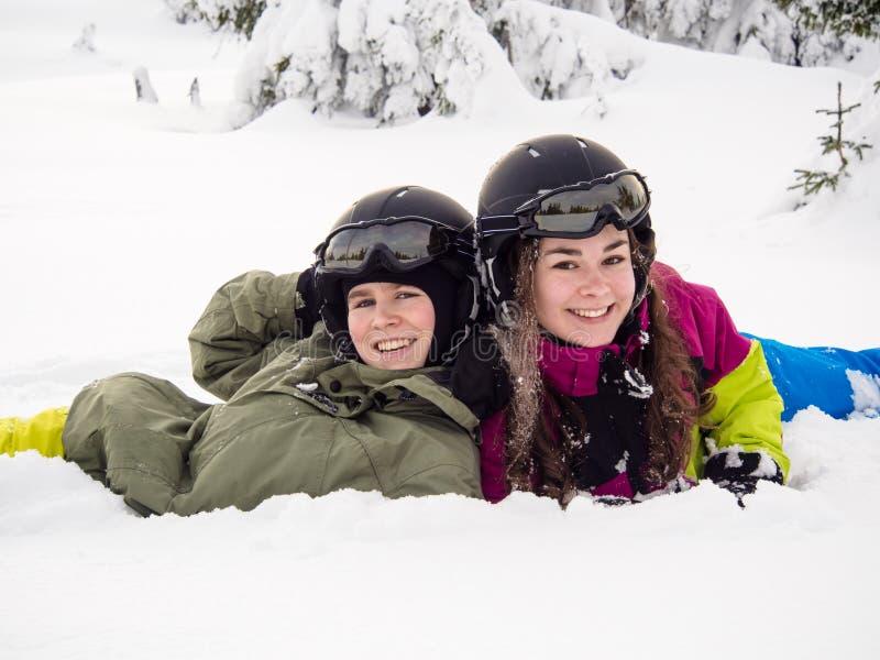 十几岁的女孩和男孩滑雪 免版税图库摄影