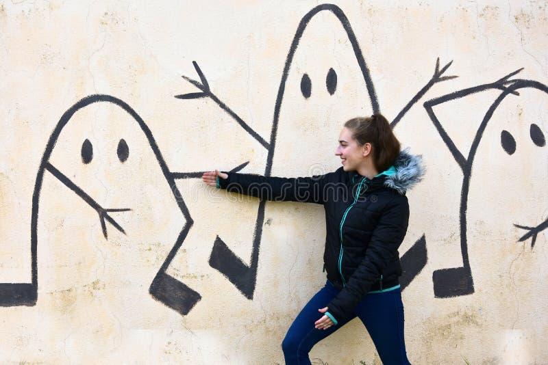 十几岁的女孩和街道画墙壁 图库摄影