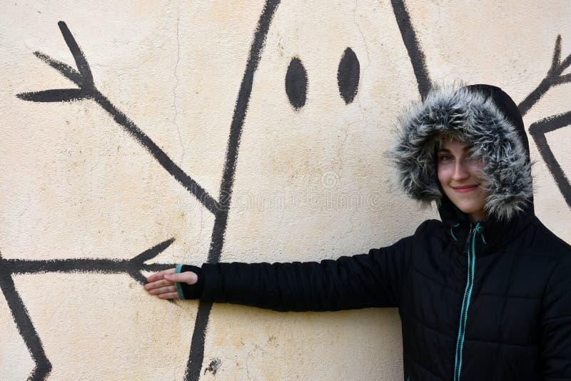 十几岁的女孩和街道画墙壁 库存图片