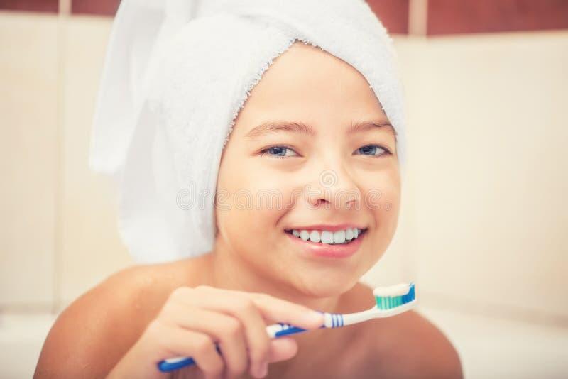 十几岁的女孩在有牙刷的卫生间里 牙齿卫生学 免版税图库摄影