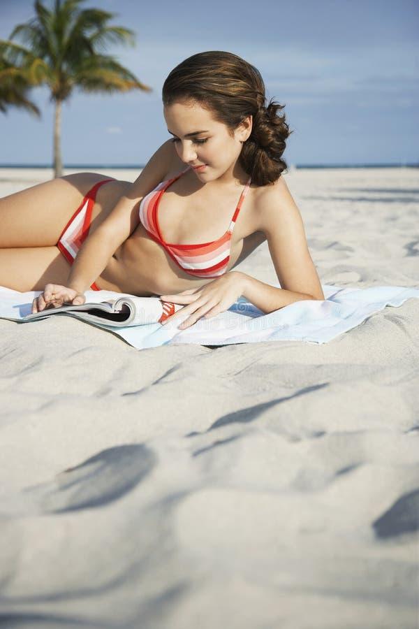 十几岁的女孩在海滩的读书杂志 免版税库存图片