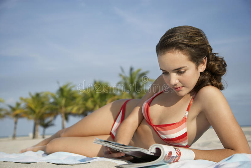 十几岁的女孩在海滩的读书杂志 库存照片