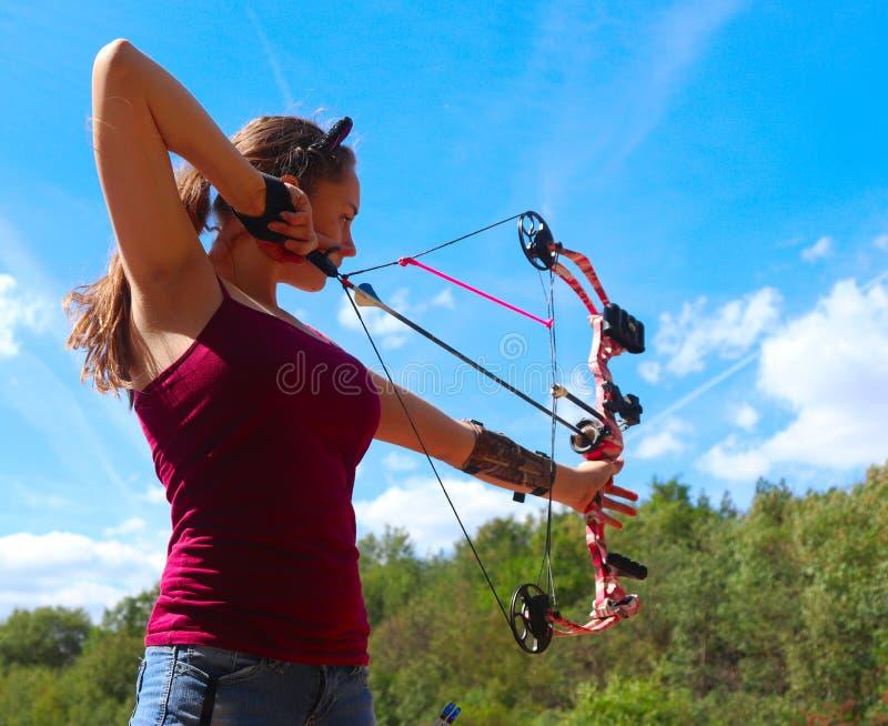 十几岁的女孩在温暖的实践射箭,夏日 库存照片