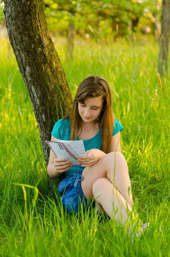 十几岁的女孩在自然的读书信件 图库摄影