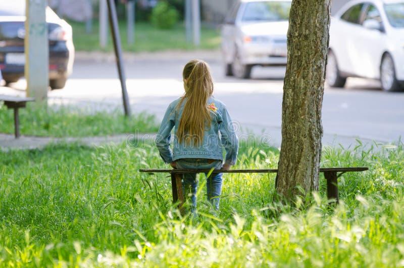十几岁的女孩坐长凳在一棵树附近在房子的庭院里 免版税图库摄影