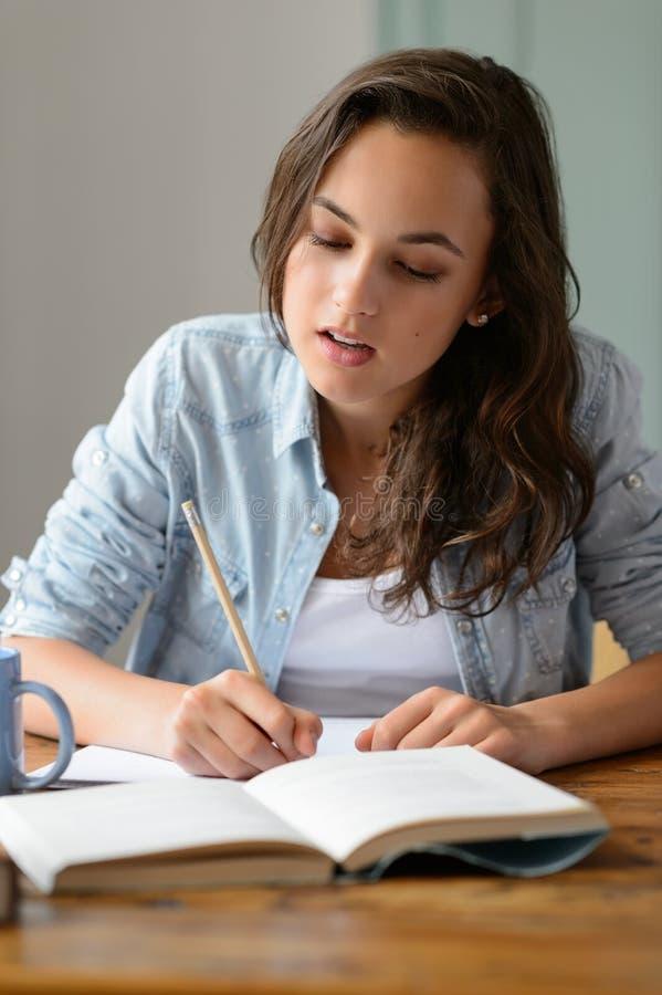十几岁的女孩学习参考书文字笔记 免版税图库摄影