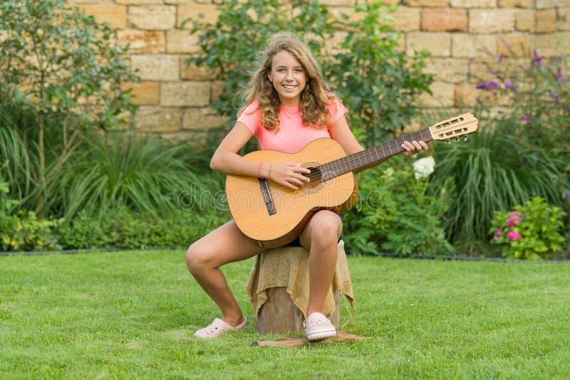 十几岁的女孩室外画象有吉他的 免版税图库摄影