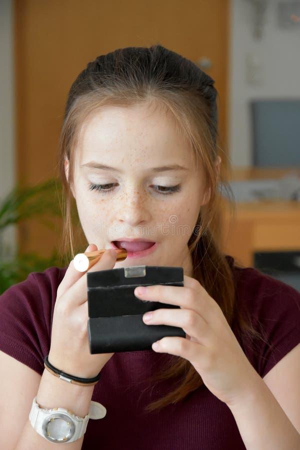 十几岁的女孩应用唇膏 免版税库存照片