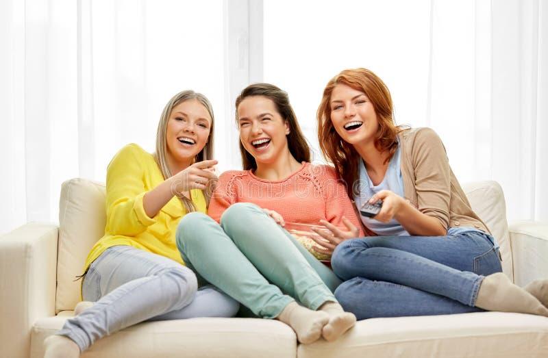 十几岁的女孩或朋友看着电视在家 图库摄影