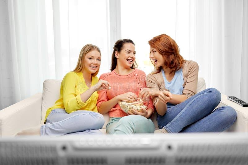 十几岁的女孩或朋友看着电视在家 免版税图库摄影