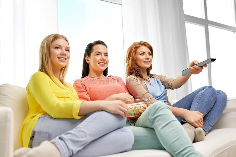 十几岁的女孩或朋友看着电视在家 库存图片