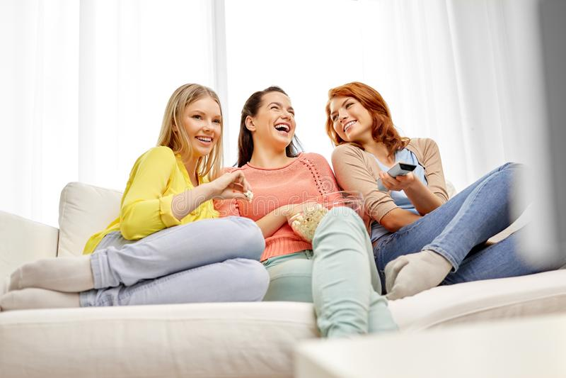 十几岁的女孩或朋友看着电视在家 库存照片
