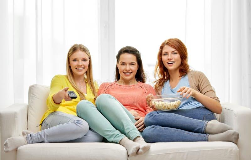 十几岁的女孩或朋友看着电视在家 免版税库存图片
