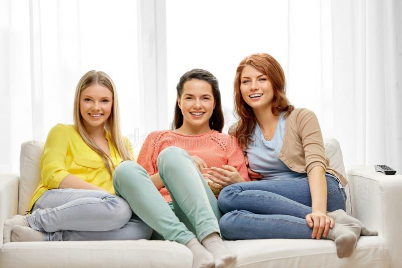 十几岁的女孩或朋友看着电视在家 免版税库存照片