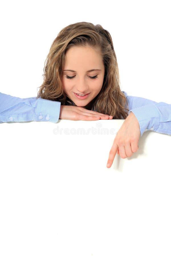 十几岁的女孩指向在空白空白符号下 库存照片