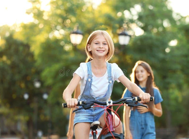 十几岁的女孩有朋友的骑马自行车在公园 免版税库存图片