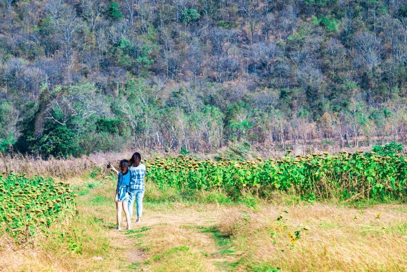 十几岁的女孩朋友夫妇走在热带森林和ta里的 库存照片