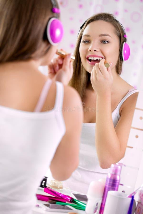 十几岁的女孩申请组成和看在镜子, 免版税库存图片