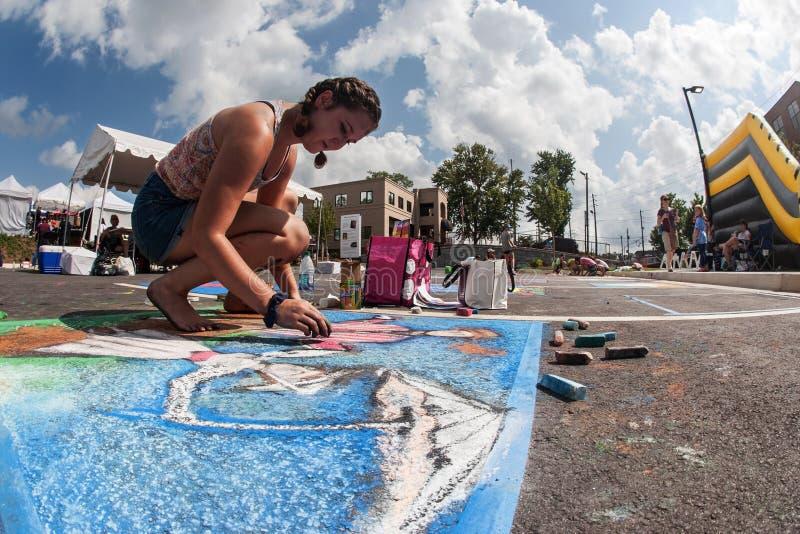 十几岁的女孩画在路面的白垩艺术在节日竞争 图库摄影