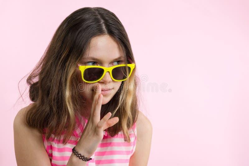 十几岁的女孩画象告诉秘密和闲话 背景桃红色,演播室 免版税库存照片