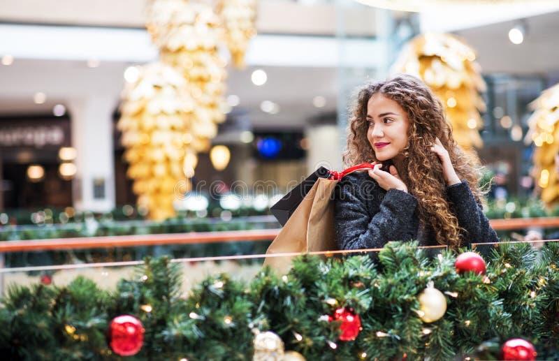 十几岁的女孩画象有纸袋的在圣诞节的购物中心 免版税图库摄影