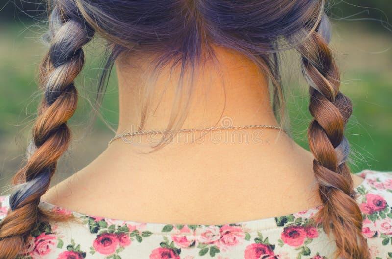 十几岁的女孩的美丽的扭转的头发从后面的在蓝色死了 库存照片