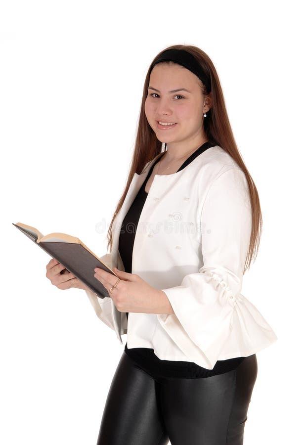 十几岁的女孩站立的白色夹克在手上的拿着一本书 免版税库存图片