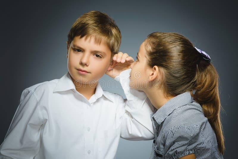 十几岁的女孩耳语在男孩的耳朵灰色背景的 黑色通信概念收货人电话 库存照片