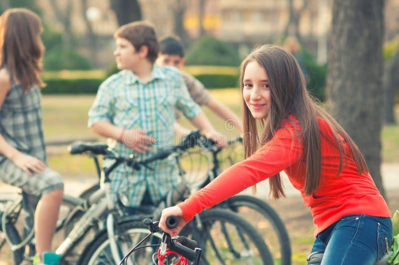十几岁的女孩获得在自行车的乐趣有她的朋友的在春天公园 库存图片