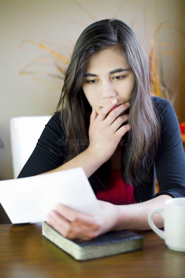 十几岁的女孩读取附注,担心的表达式 库存图片