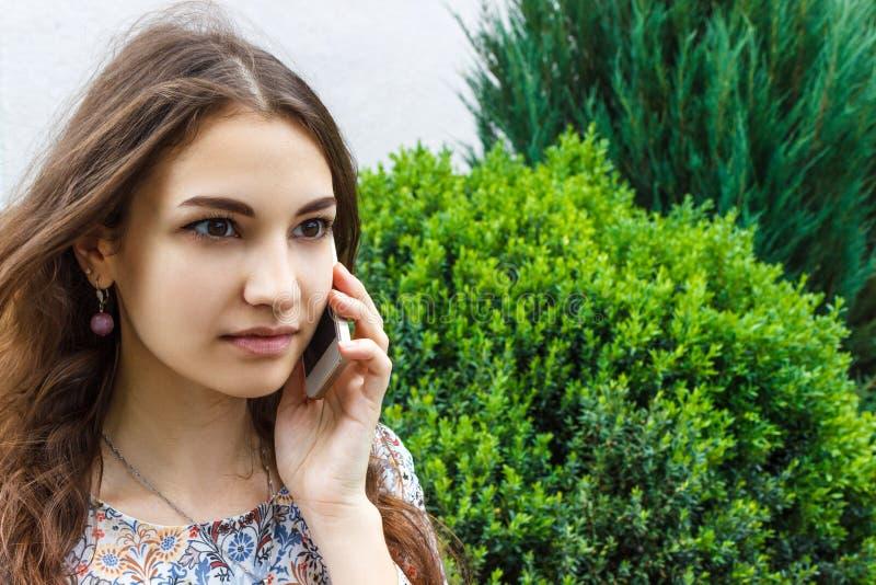 十几岁的女孩谈话在电话在办公楼附近 免版税库存照片