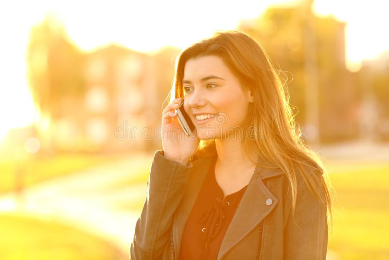 十几岁的女孩谈话在电话在日落 库存照片