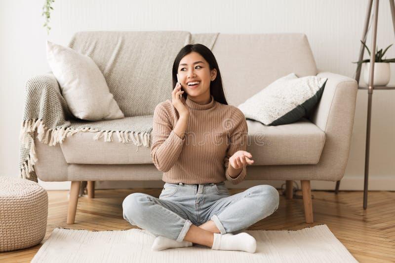 十几岁的女孩谈话在电话,坐地板在沙发附近 免版税图库摄影