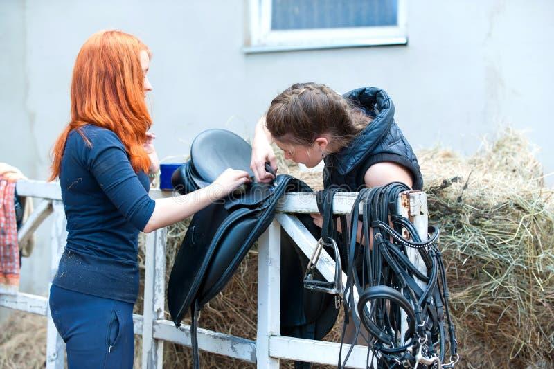 十几岁的女孩骑马者清洗黑皮革马马鞍 免版税库存照片