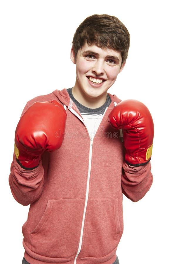 年轻十几岁的男孩佩带的拳击手套微笑 免版税库存照片
