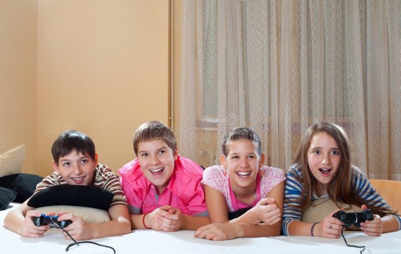 十几岁的男孩和女孩作用电脑游戏 库存照片