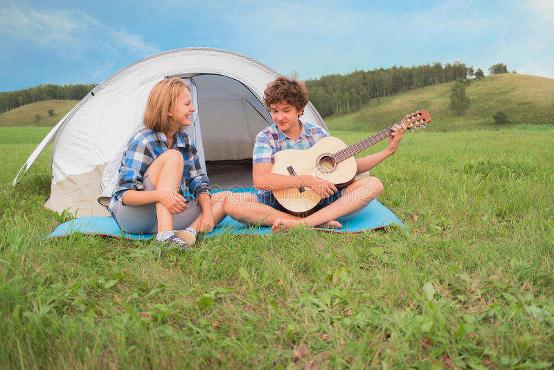 十几岁的男孩和女孩在帐篷附近弹吉他 免版税库存图片